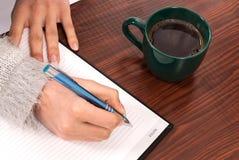 写入笔记本的妇女在木书桌和饮料咖啡 免版税库存图片