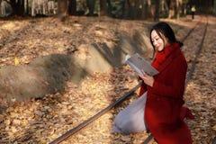 写入自然是我的爱好,女孩读了书充分坐路轨银杏树biloba叶子 库存图片