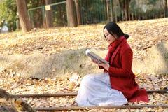 写入自然是我的爱好,女孩读了书充分坐路轨银杏树biloba叶子 免版税库存照片