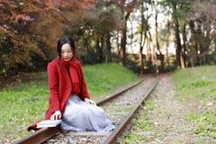 写入自然是我的爱好,女孩读了书坐路轨 库存照片