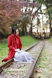 写入自然是我的爱好,女孩读了书坐路轨 免版税库存照片
