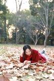 写入自然是我的爱好,女孩读了充分说谎槭树叶子的书 免版税图库摄影