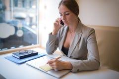 写公证员的年轻女性企业主在贴纸在手提电脑的工作以后 库存照片