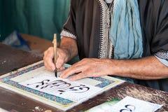写关于宣纸的羊皮纸的老手 库存图片