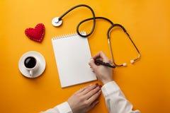 写医疗记录的专业医生在有听诊器、咖啡杯、注射器和心脏的一个笔记本 免版税库存图片