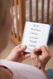 写可能的名字的妇女为男婴在托儿所 免版税库存图片