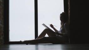 写图片的女孩艺术家的剪影在一个大窗口附近 影视素材