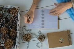写圣诞老人信的女性手在与圣诞装饰、冷杉球果、笔记薄和蓝色的白色木背景 库存图片