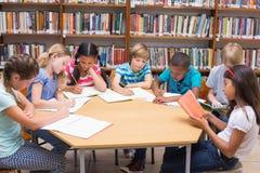 写在书桌的逗人喜爱的学生在图书馆 免版税库存照片