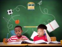 写在书桌的逗人喜爱的学生的综合图象在教室 库存图片