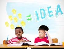 写在书桌的逗人喜爱的学生的综合图象在教室 库存照片