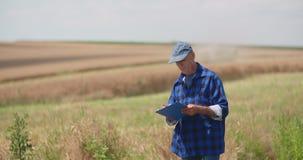 写在剪贴板的成熟男性农夫在农场 现代农业 股票视频