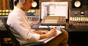 写在剪贴板的男性音频工程师 股票录像