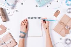 写在圣诞节装饰中的一个笔记本的女性手 免版税库存照片