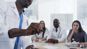 写在委员会的男性医生接近的射击在lection时在年轻实习生在会议室 股票视频