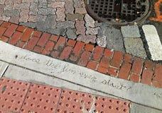 写在混凝土在一条肮脏的都市街道 免版税库存图片
