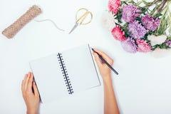 写在空白的笔记薄的女性的手在平的被放置的假日b中 免版税图库摄影
