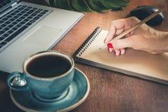 写在笔记本的女性手 在老笔纤管滚动葡萄酒文字黄色附近仍然登记概念生活 免版税图库摄影