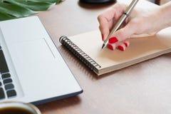 写在笔记本的女性手 在老笔纤管滚动葡萄酒文字黄色附近仍然登记概念生活 免版税库存照片