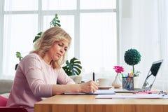 写在笔记本的年龄30-40的快乐的夫人,当坐在时 库存照片