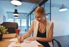 写在膝上型计算机前面的企业白肤金发的女孩一本书 免版税库存照片