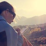 写她的想法的女性旅客在日落 免版税库存照片