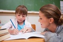 写她的老师谈话的一会儿的逗人喜爱的女小学生 免版税图库摄影