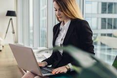 写广告文本的年轻女性撰稿人键入在坐膝上型计算机的键盘在办公室 免版税库存照片