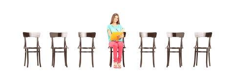 写微笑的女学生坐一把木椅子和没有 库存照片