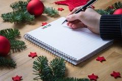 写愿望圣诞节的在与圣诞节de的一个笔记薄 免版税库存照片