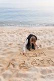 写新年的女孩在沙子 库存照片