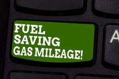 写显示节约燃料汽油里程的笔记 陈列企业的照片消费在车费用气体的较少金钱 库存照片
