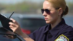 写本地报告在巡逻车附近,公路事故的严肃的巡逻妇女 股票视频