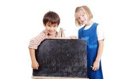 写材料的Schoolkids在黑板 免版税图库摄影