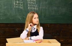 写某事的殷勤学生在他们的笔记本,当坐在书桌在教室时 与合格的教训 库存图片