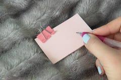 写桃红色笔在与桃红色金属钳位文具的浅粉红色的贴纸 免版税库存照片