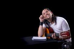 写歌曲的吉他弹奏者音乐家在他的吉他 库存图片