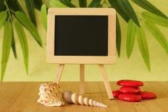 写消息的小空的黑板在一个木地板上的一个画架摆在了与在一片绿色叶子的红色小卵石和海滩壳 库存图片