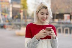 写消息的美丽的妇女在她的电话,当做shopp时 免版税库存图片