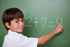 写添加的愉快的男小学生 免版税库存图片