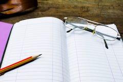 写生簿或笔记本有铅笔的在老木表上 免版税库存照片