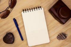 写生簿空白页与笔、照片照相机和太阳镜的在木台式视图 葡萄酒行家背景 免版税库存照片