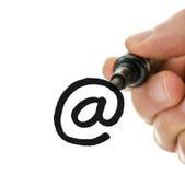 写电子邮件标志的男性手在玻璃委员会 免版税库存照片