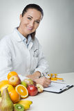 写病历的微笑的营养师 免版税图库摄影
