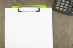 写白纸夹子在有计算器的绿色剪贴板 免版税图库摄影