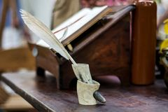 写的中世纪翎毛钢笔在从垫铁的墨水池在木书桌 免版税图库摄影