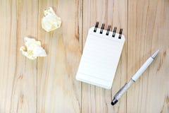 写的信息小笔记本纸笔记薄与笔和被弄皱的纸球在木桌 库存照片