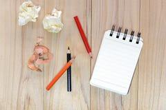 写的信息小笔记本纸笔记薄与颜色铅笔和被弄皱的纸球在木桌 免版税库存图片