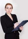 写的有吸引力的精力充沛的女商人压料板和采取笔记 库存图片