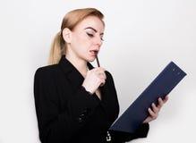 写的有吸引力的精力充沛的女商人压料板和采取笔记 图库摄影